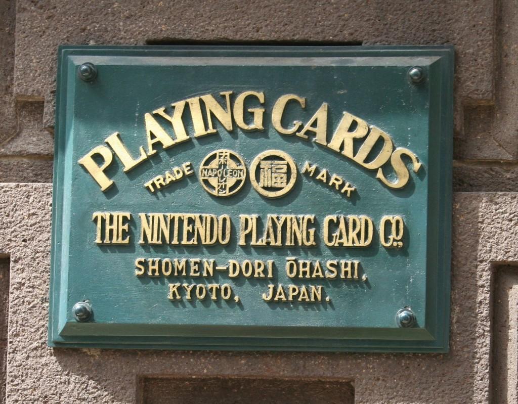 Plaque de la société à l'emplacement des anciens bureaux principaux de cartes à jouer de Nintendo, à Kyoto, au Japon, devenu plus tard la célèbre compagnie de jeux vidéos. Dans le cercle de gauche est inscrit «NAPOLEON» en caractères latin et l'équivalent en katakana (ナポレオン). Dans le cercle de droite, le traditionnel caractère chinois de la bonne fortune.