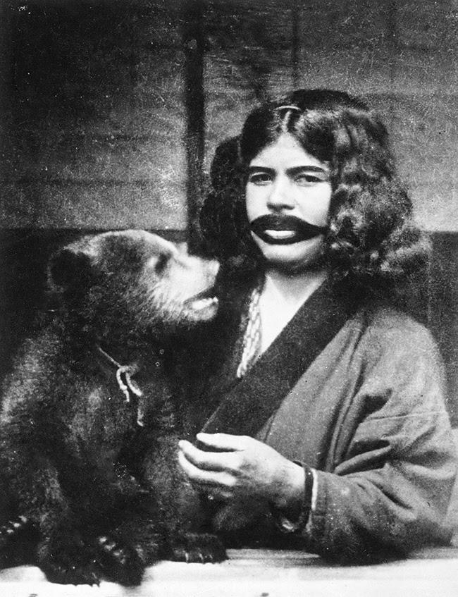 Une Aïnou à la bouche tatouée, tenant un ourson sauvage (1922).